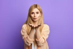 Ehrfürchtige schöne Blondine in der stilvollen Kleidung, die Luftkuß zur Kamera durchbrennt lizenzfreie stockbilder