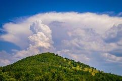 Ehrfürchtige Wolken über dem grünen Hügel Lizenzfreie Stockfotos