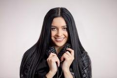 Ehrfürchtiges dunkelhaariges Modell, das den Kragen der schwarzen Lederjacke hält stockbild