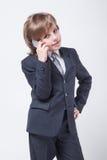 Ehrgeiziges junges erfolgreiches Kind in einem Anzug und Bindung sprechen Lizenzfreies Stockbild