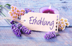 Ehrhohlung - revitalization and wellness. Background with a handwritten label with the word - Ehrhohlung - in German with a burning aromatherapy candle and Stock Photography