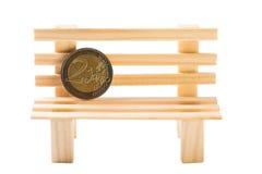 Ei auf goldenem Hintergrund Münze des Euros zwei auf der dekorativen Holzbank lokalisiert auf Weiß Stockfotos