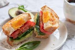 Ei in een gatensandwich met avocado, spinazie en tomaat royalty-vrije stock foto's