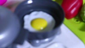 Ei in een stuk speelgoed plastic pan wordt gebraden die