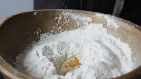 Ei fällt auf hölzerne Schüssel mit Mehl stock video