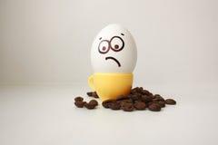 Ei met een gezicht Grappig en leuk aan een koffiemok stock afbeelding