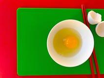 Ei met eetstokjes op scherpe raad stock fotografie