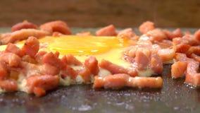 Ei met fijngehakt die bacon op de grill wordt gebraden stock video