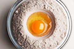 Ei mit Mehl auf einer Platte Stockbild