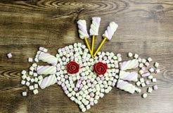 Eibische, die das Herz auf Holztisch formen stockbild
