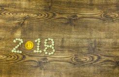 Eibische und goldenes bitcoin als Symbol von 2018 Geschäftsjahr auf Holz Lizenzfreies Stockbild