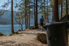 Eibsee, Germany, March 31, 2019: trash can next to the seeweg loop track with a jogging man. The trash cans are spread all over stock photos