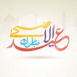 Eid-Al-Adha celebration with arabic calligraphy text. Colorful arabic calligraphy text Eid-Al-Azha Mubarak on mosque silhouette background for muslim community Royalty Free Stock Photography