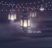 Eid al adha. Greeting card template on Eid Al-Fitr muslim religious holiday with lanterns on blurred lights background Stock Image
