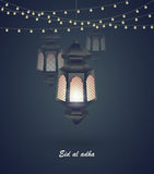 Eid al adha. Greeting card template on Eid Al-Fitr muslim religious holiday with lanterns on blurred lights background Royalty Free Stock Image