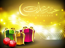 Eid Mubarak background. Arabic Islamic calligraphy of golden text Eid Mubarak with gift boxes on beautiful background for Eid festival. EPS 10 Royalty Free Stock Images