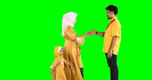 Happy muslim family kissing father hands. Eid Mubarak concept. Happy muslim family with young mother and two kids wearing islamic clothes and kissing their stock video