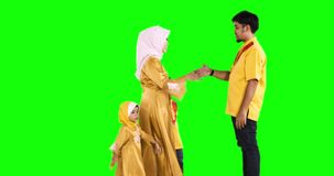 Happy muslim family kiss father hands. Eid Mubarak concept. Happy muslim family with young mother and two kids wearing islamic clothes and kissing their father stock video footage