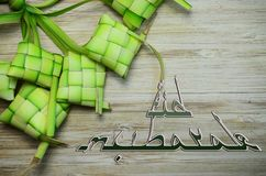 Eid mubarak mean greeting after ramadhan fast with coconut rice casing on wooden background. Eid mubarak greeting ramadhan  fast  casing coconut rice wooden royalty free stock images