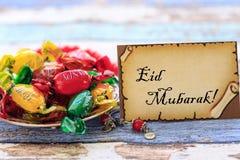 Eid mubarak på kortet med färgrika godisar på tappningtabellen royaltyfri bild