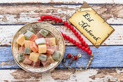 Eid mubarak text on the card with red rosary and turkish delight Stock Photography