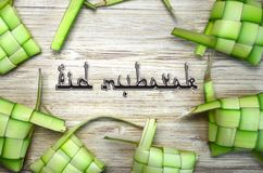 Eid mubarak text with rice casing on wooden background. Eid mubarak text rice casing wooden background muslim food royalty free stock image