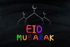 Eid Mubarak, traditional Muslim greeting . On black broad.  Royalty Free Stock Photos