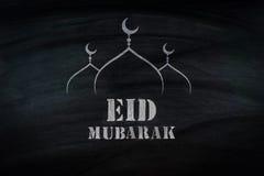 Eid Mubarak, traditional Muslim greeting . On black broad.  Royalty Free Stock Photo