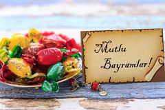 Eid mubarak in turkish on the card with colorful candies on vint. Age table close up Royalty Free Stock Image