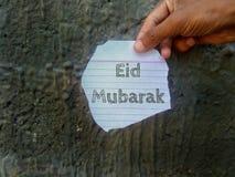 Eid Mubarak-wensen op een stuk van document holding die ter beschikking worden geschreven royalty-vrije stock afbeeldingen