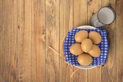 Eier auf blauem Tuch in der keramischen Schüssel auf Holztisch mit Glas Milch Getrennt auf weißem Hintergrund vektor abbildung