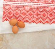 Eier auf der Tischdecke mit einem roten Muster Stockbilder