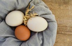 Eier auf hölzernem Nahrungsmittelstrohhuhn stockfotos