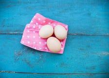 Eier auf Tischdecke über hölzernem Hintergrund Lizenzfreies Stockfoto