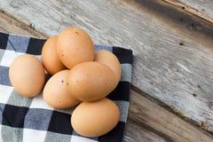 Eier auf Tischdecke über Holztisch Stockfoto