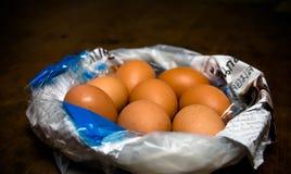 Eier auf Zeitung in der Plastiktasche auf dunkelbraunem Holztisch Stockfotos