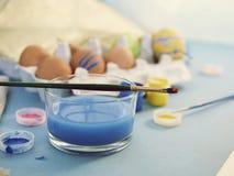Eier, bunte Farben, Bürsten, Bleistifte auf einem blauen Hintergrund lizenzfreie stockfotografie