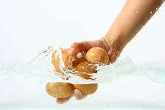 Eier in der Hand in klares Wasserspritzen stockfoto