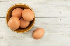 Eier in der keramischen Schüssel auf Holztisch Stockfotografie