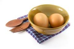Eier in der Schüssel mit hölzernem Löffel und Gabel Lizenzfreies Stockbild