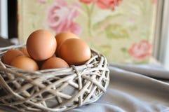 Eier in einem hölzernen Korb Stockbild