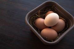 Eier in einem Kasten auf einem braunen hölzernen Hintergrund Lizenzfreie Stockbilder
