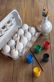 Eier in einem Kasten, in einer farbigen Farbe, in einer Bürste und in Bleistiften Stockfotografie