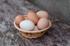 Eier in einem Korb auf einem hölzernen Hintergrund Stockfotos