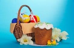 Eier in einem Korb, in einem Ostern-Kuchen und im Blumenstrauß lizenzfreies stockbild
