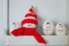 Eier in einem lustigen Hut mit einem Karikaturgesicht gemalt Stockbilder