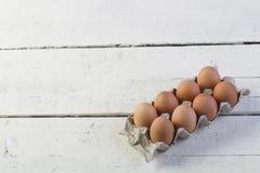 Eier in einem Pappbehälter auf weiße Bretter Lizenzfreie Stockfotos