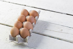 Eier in einem Pappbehälter auf weiße Bretter Stockfotografie