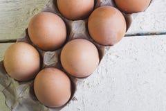 Eier in einem Pappbehälter auf weiße Bretter Lizenzfreies Stockfoto