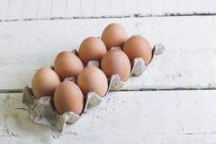 Eier in einem Pappbehälter auf weiße Bretter Stockbilder